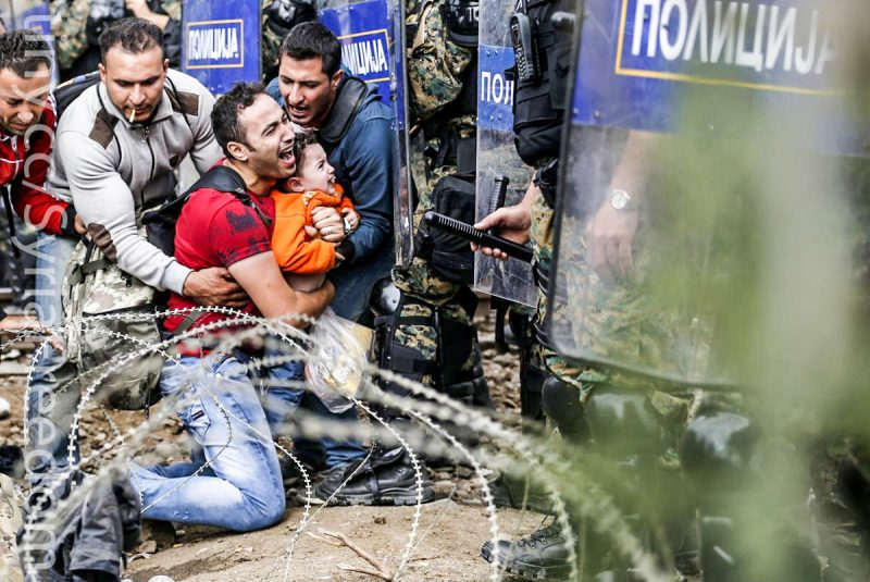 Migrant men help a fellow migrant man holding a boy as they are stuck between Macedonian riot police officers and migrants during a clash near the border train station of Idomeni, northern Greece, as they wait to be allowed by the Macedonian police to cross the border from Greece to Macedonia, Friday, Aug. 21, 2015. Macedonian special police forces have fired stun grenades to disperse thousands of migrants stuck on a no-man's land with Greece, a day after Macedonia declared a state of emergency on its borders to deal with a massive influx of migrants heading north to Europe. (AP Photo/Darko Vojinovic) (Darko Vojinovic)