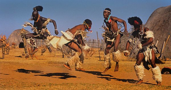 Many African dances involve jumping including ritual dances of the Zulu. In the background are the typical traditional Zulu huts and vegitation (aloes) of the higher regions of Kwazulu Natal, South Africa. Photo by Hein waschefort.