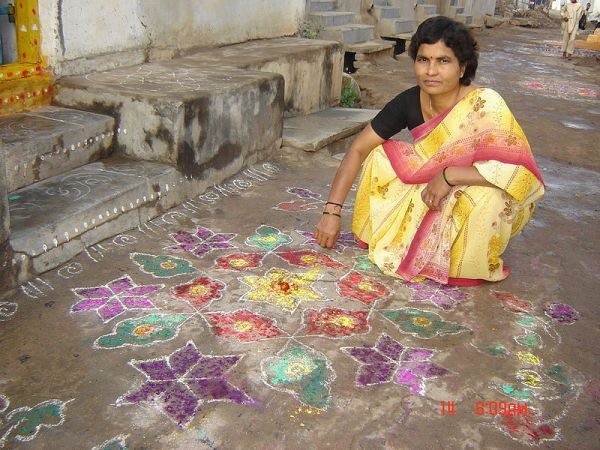 A woman drawing Muggu (coloured patterns) in front of their home during the Sankranthi Festival. Photo by  Mr. Chidambar Rao Bhukya.