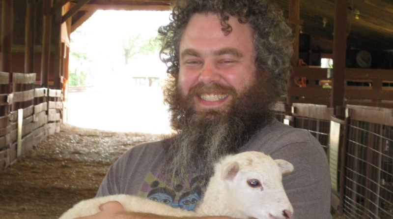 Patrick Rothfuss holding a goat at Heifer International Headquarters.