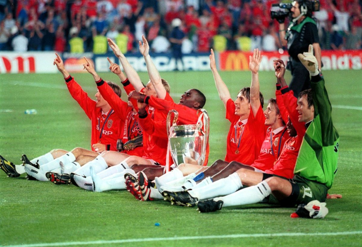 Manchester United players celebrate with the coveted Champions League trophy infront of the traveling fans after their historic win