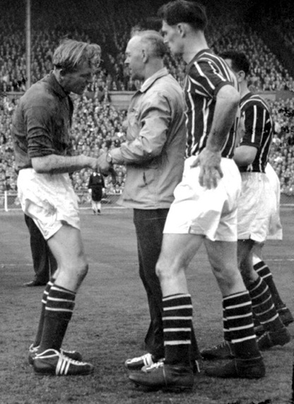 Manchester City trainer Laurie Barnett checks on the condition of groggy goalkeeper Bert Trautmann during the 1956 FA Cup Final against Birmingham (Source: www.whoateallthepies.tv)