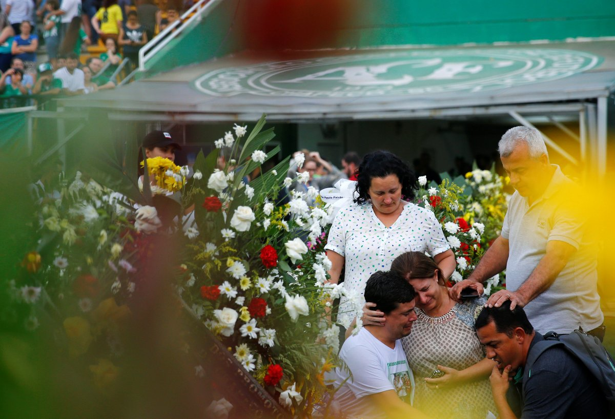 Relatives of Sergio de Jesus cry in front of flowers dedicated to him during a gathering [Source: Yahoo]