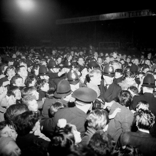 Police struggle to get Bert Trautmann through the swarm of fans who mobbed him after his testimonial at Maine Road in 1964 (Source: www.whoateallthepies.tv)