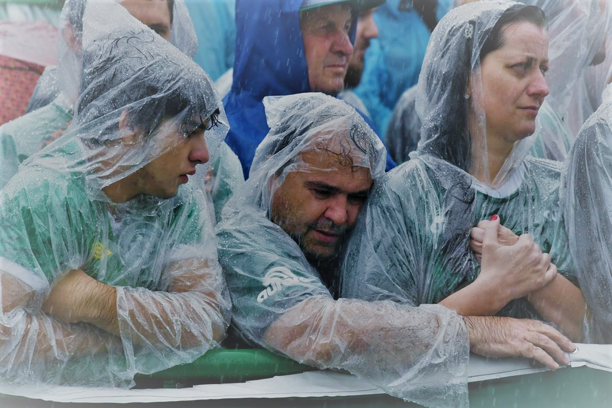 Fans wait in the rain for the arrival of the coffins of members of the Chapecoense team. [ Nelson Almeida / AFP - Getty Images ]