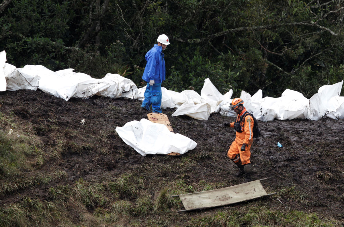 Rescue workers walk next to bodies of victims from the wreckage of a plane that crashed into the Colombian jungle with Brazilian football team Chapecoense onboard near Medellin, Colombia, November 29, 2016. REUTERS/Jaime Saldarriaga