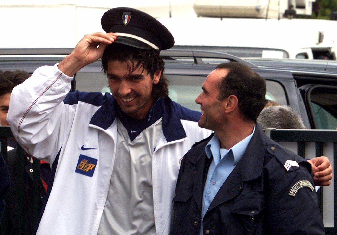 Italy's reserve goalkeeper Gianluigi Buffon jokes with a policeman at the end of a news conference at the Italian training base in Senlis June 14. Italy will meet Cameroon in their next World Cup group B match on June 17 in Montpellier. VP/KM - RTRVQLE
