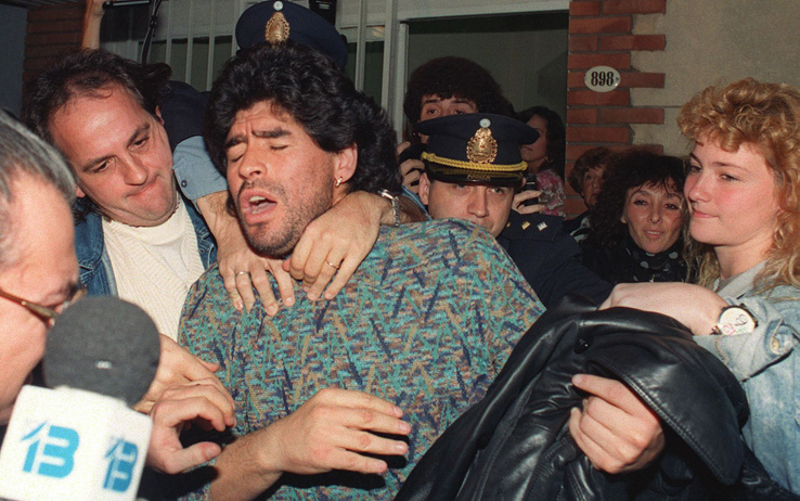 (FILES) Argentinian soccer player Diego Maradona (C) is removed by police from a Buenos Aires apartment, 26 April 1991, after being arrested for possession of half-kilo of cocaine. Maradona was suspended by the Italian League 29 March 1991, after an analysis of his urine tested positive for cocaine. (Photo credit should read DANIEL LUNA/AFP/Getty Images)