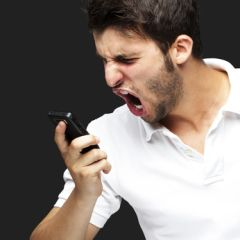 portrait of angry young man shouting using mobile over black bac
