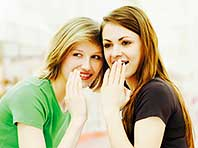 Two young women, friends, whispering and  gossiping - ibxaib03035865.jpg