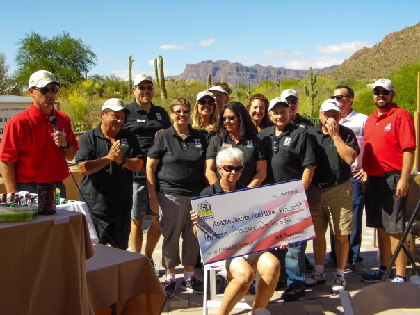 Jim McMahon, FAAMA Western Pacific Regional Director (left), and Nick Engebretson, FAAMA Chapter 262 and Golf Director (right), present the $13,000 check to representatives from the Apache Junction Food Bank.