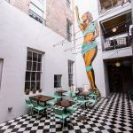 The courtyard at the Catahoula Hotel features a larger-than-life mural of local burlesque artist Trixie Minx. (Courtesy photo)