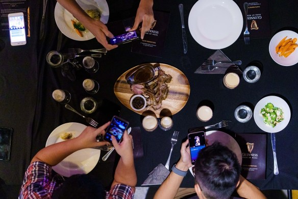 Guests taking pictures of the exclusive main course dish during the GUINNESS Draught Taste Perfection Media Dinner at Makhan by Kitchen Mafia