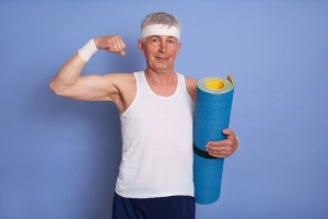 Energetic senior man has physical training, holding yoga mat, showing biceps and his power, looking at camera with pleased expression, warming up body before training.