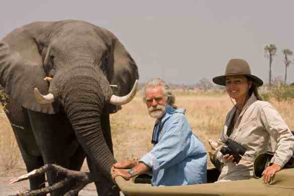 Wildlife Filmmakers Dereck and Beverly Joubert inside their production 4x4 vehicle near an adult elephant.