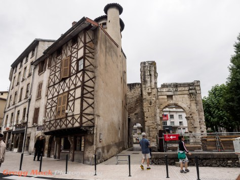 A Medieval house on the left, next to some Roman ruins in Vienne.
