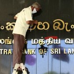A man cleans the main board of the Central Bank of Sri Lanka in Colombo.
