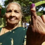 A Tamil woman shows her ink-marked finger after she cast her vote during a local government election in Jaffna