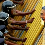 Police take up position behind a metal barrier as students from a group of universities hold a puppet of Sri Lanka's President Rajapaksa over the barrier during a protest in Colombo