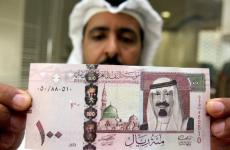 A Saudi banker displays the new one hund