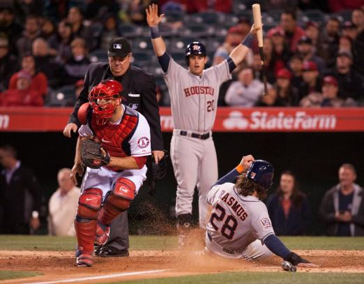 Houston's Colby Rasmus scores past Angels catcher Chris Iannetta during a three run bottom of the ninth during the Halos' a 3-2 loss to the Houston Astros Thursday night at Angel Stadium. ///ADDITIONAL INFO:    angels.0508.kjs  ---  Photo by KEVIN SULLIVAN / Orange County Register  --  5/7/15 The Los Angeles Angels take on the Houston Astros Thursday night at Angel Stadium.
