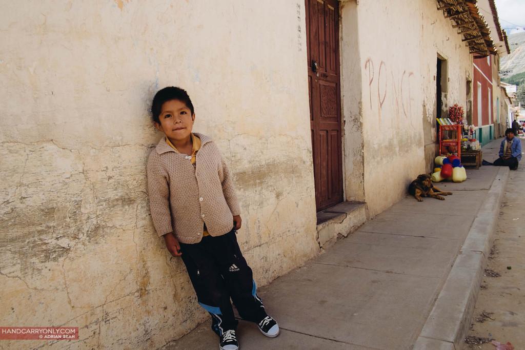 boy standing by wall, tarabuco, bolivia