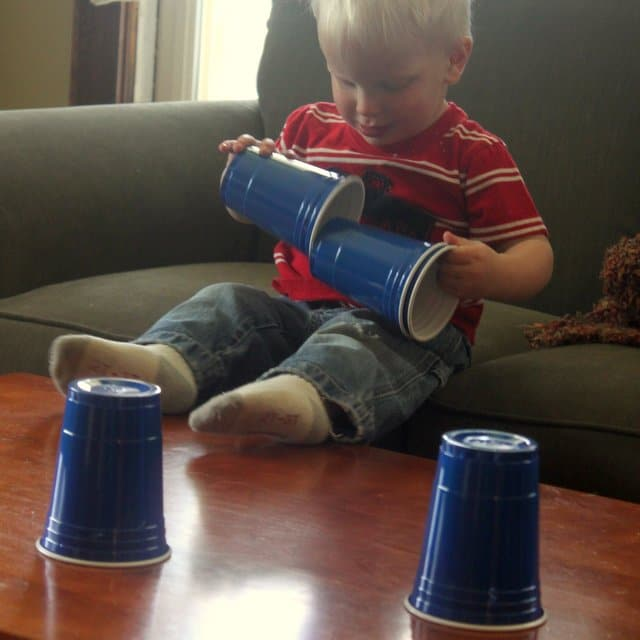 Toddler playing with plastic cups