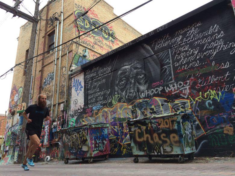 men running down graffiti alley