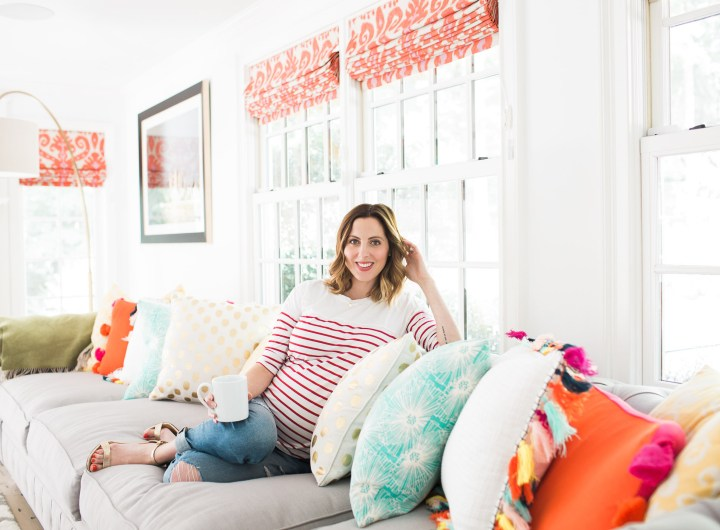 Eva Amurri Martin of lifestyle blog Happily Eva After relaxes at home in her family room on a grey couch with multicolored and multipatterned pillows surrounding her, holding a cup of coffee