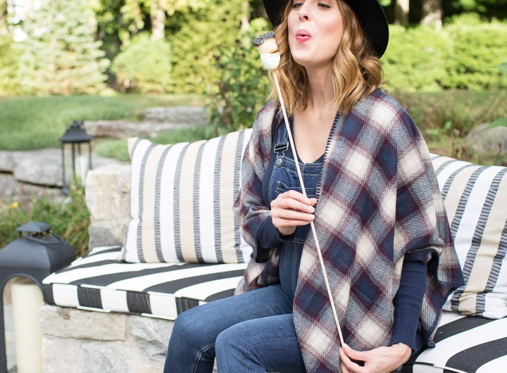 Eva Amurri Martino of lifestye and motherhood blog Happily Eva After at her firepit at her connecticut home, wearing maternity overalls, a navy felt hat, and a plaid poncho roasting marshmallows over the fire
