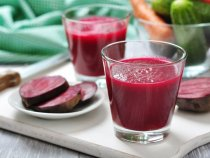 Beetroot juice in glass on  wooden cutting board