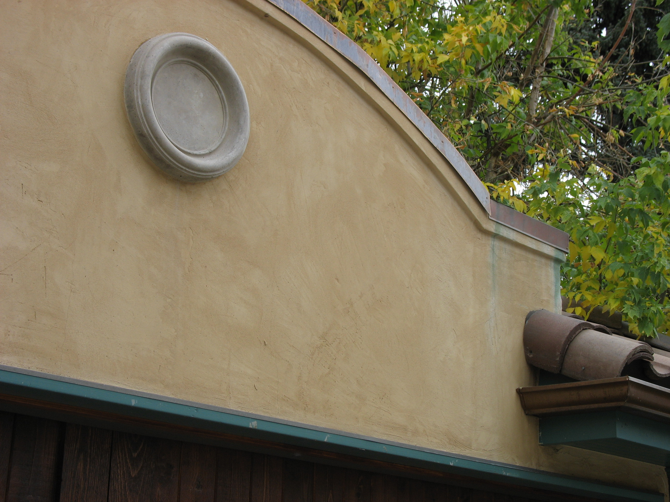 Close-up of stucco wall with red tile roof