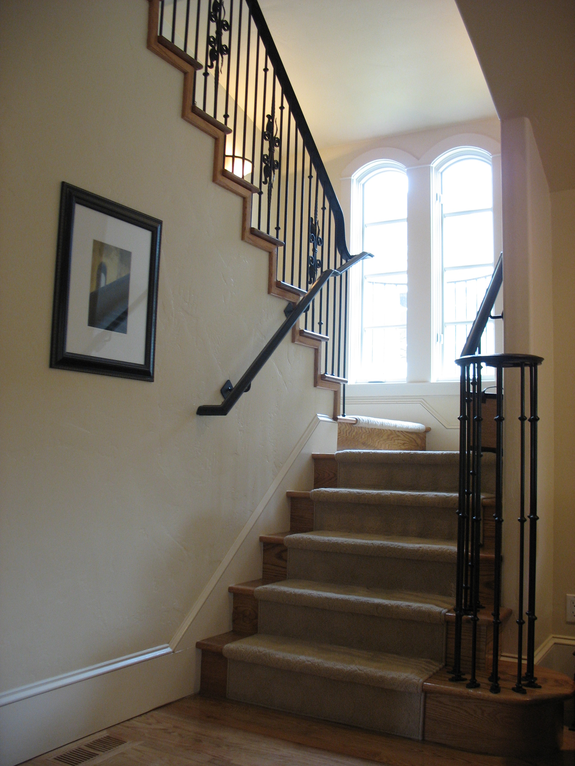 Looking up wrought iron and wood staircase
