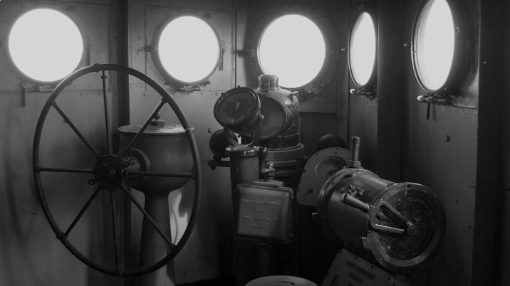 The wheelhouse of this WWI-era vessel is a lot more sparse than that of a modern-day ship; notice the ferromagnetic compensators on the binnacle with the compass.