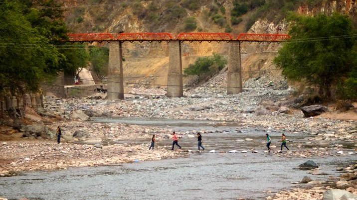 Women hopping rocks to cross the shallow river.