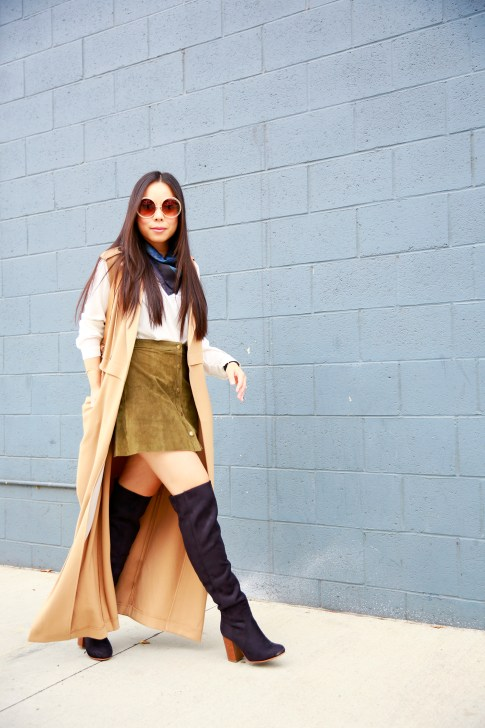 An Dyer wearing Hermes Pocket Square Around Neck, Olive Suede Button Front Skirt Sleeveless Trench Duster, suede Over The Knee Boots