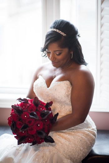 Beautiful Toronto bride holding deep red and dark coloured leaf bouquet before her wedding