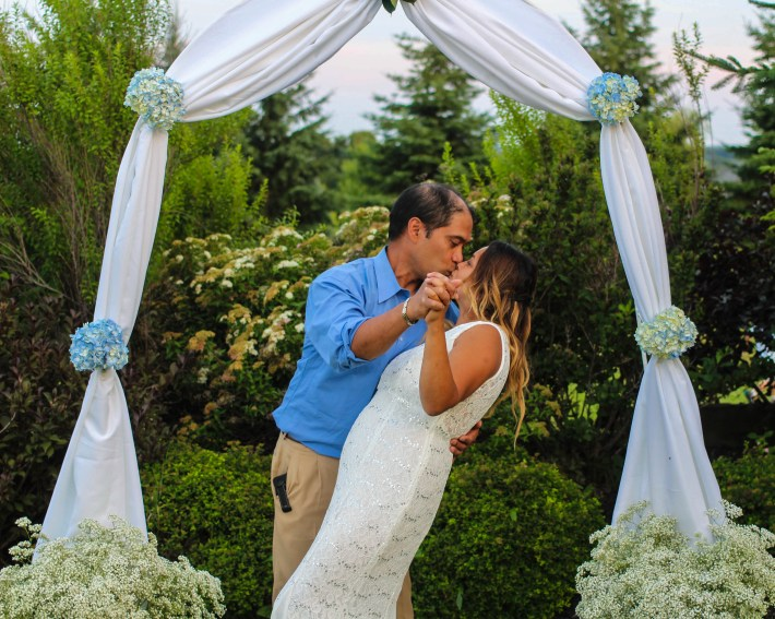 Beautiful couple under blue floral arch in outdoor wedding