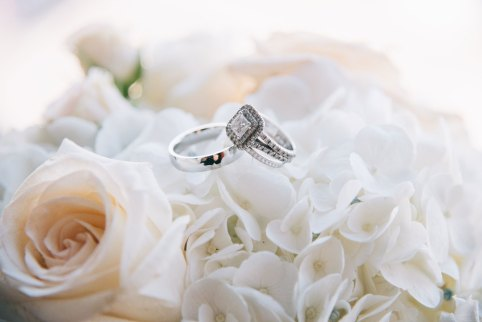 Wedding rings sitting on top of white and light pink floral bouquet