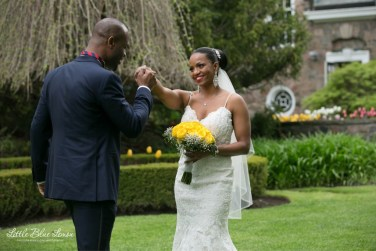 Beautiful bride holding yellow rose bouquet and handsome husband at outdoor wedding