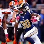 St. Louis Rams running back Todd Gurley (30) runs between Cleveland Browns defensive end John Hughes III (93) and strong safety Donte Whitner on his way to a 48-yard gain during the third quarter of an NFL football game Sunday, Oct. 25, 2015, in St. Louis. (AP Photo/Billy Hurst)