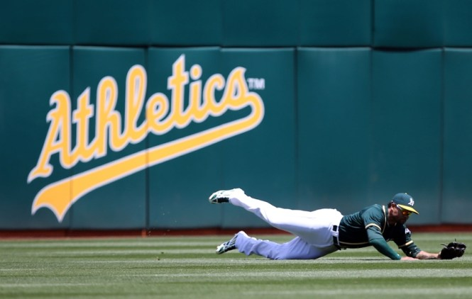 May 13, 2015; Oakland, CA, USA; Oakland Athletics left fielder Coco Crisp (4) makes a diving catch against the Boston Red Sox during the fifth inning at O.co Coliseum. Mandatory Credit: Kelley L Cox-USA TODAY Sports