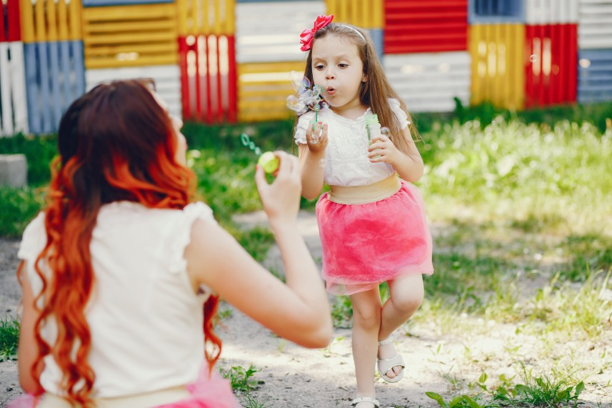 beautiful and bright redhead mother dressed in a white T-shirt and a pink skirt walks in a sunny summer park with her little daughter who is dressed just like mom