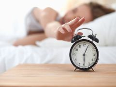 Young sleeping woman and alarm clock in bedroom at home .