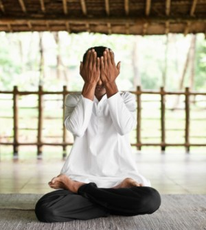 Man Practicing Yoga covers his eyes.