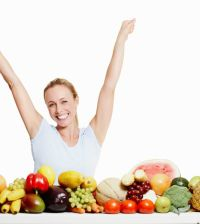 Portrait of excited woman celebrating with bunch of fruits and vegetables over white background