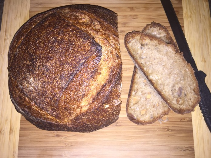 Two slices of Baldwin Brown Sourdough Bread sit on a wooden breadboard alongside a knife and a sliced loaf.