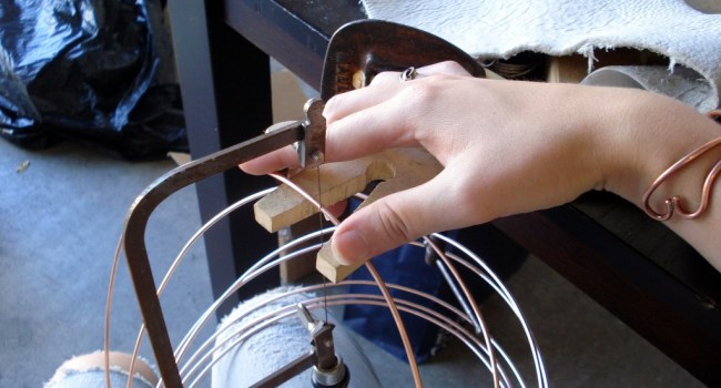 Heather using a jewelers saw to cut wire.