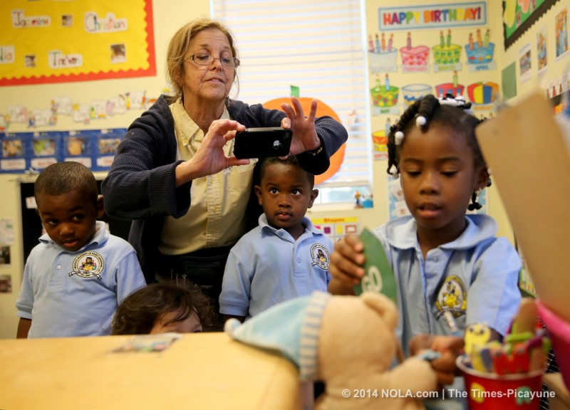 At Wilcox Academy on N. Broad Street, teacher Shelley Collen photographs Akhai Phoenix with an iPhone as the pre-K student changes a sign from red to green on Thursday, November 7, 2013. Documenting development is part of the state's new early childhood standards that are being implemented in day care centers called Teaching Strategies Gold. (Michael DeMocker, Nola.com / The Times-Picayune) No reproduction