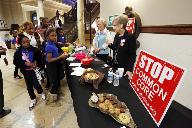 K. Butler, right of Benton, Miss., and Lynn Wagner of Hickory, second from right, speak to school children from Meridian as they are guided past their Opponents of Common Core table in the rotunda of the Mississippi State Capitol in Jackson, Miss., Tuesday, Jan. 27, 2015. The group is one of several statewide that are against a national standards Initiative that sets Math and English curriculum in every participating state at the same level. Various opposing groups lobby visiting school children, visitors and lawmakers into opposing the standards in Mississippi. Opponents have provided coffee, morning pastries and water several times during the session in an effort to promote a Senate bill that would repeal Common Core in Mississippi.